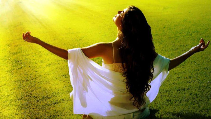 Eine Frau sitzt auf einer Wiese und breitet ihre Arme aus. Sie wirkt als würde sie sich von Altlasten befreien und entgiften.