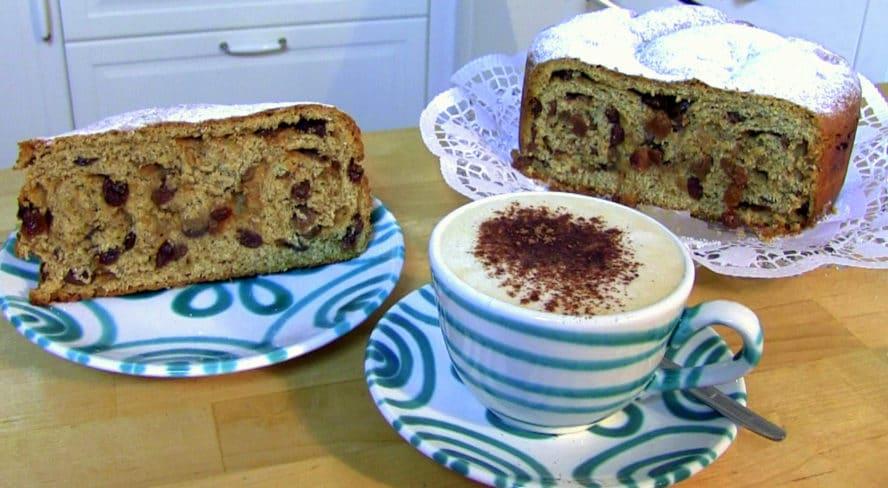 Der Kärntner Reindling ist angeschnitten und mit Kaffee serviert. Man kann schön die Füllung des Reindlings sehen.
