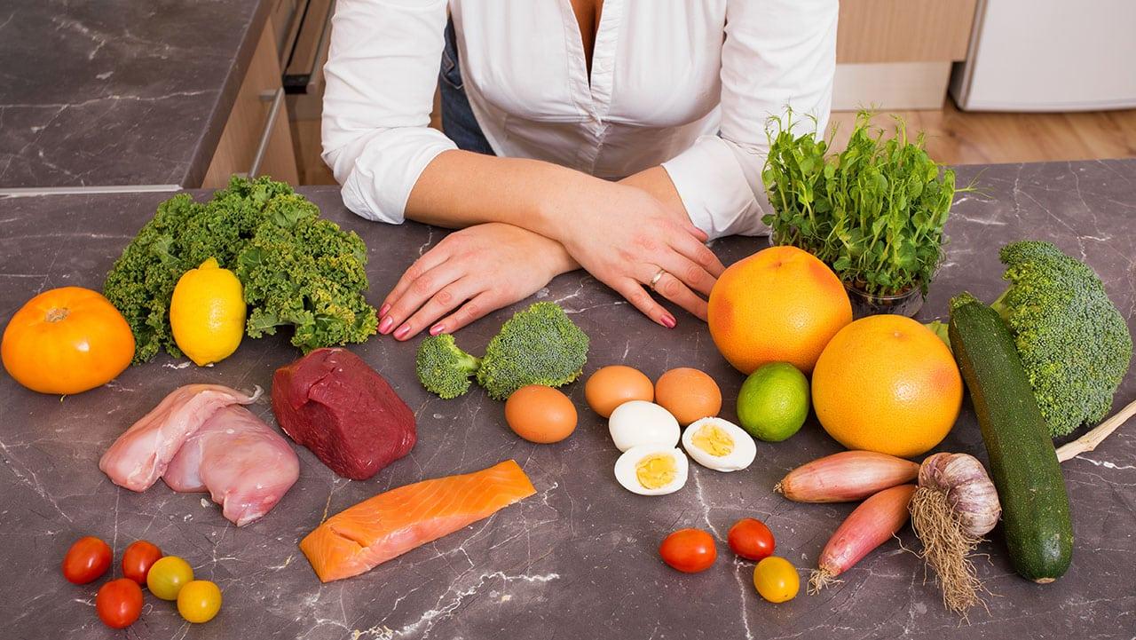 Auf einem Tisch liegen Low Carb Lebensmittel wie Fisch, Eier, Fleisch und Gemüse.