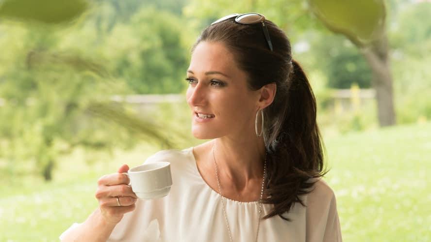 Sandra Exl hält eine Tasse Kaffee und freut sich.