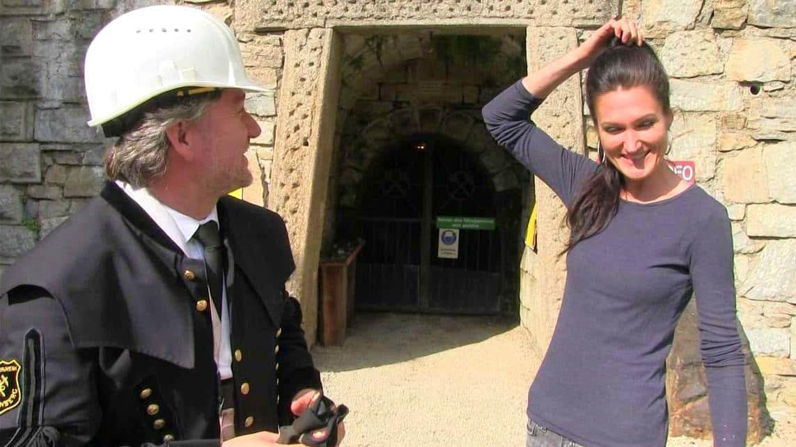 Lana steht gemeinsam mit dem Bergwerksführer vor dem Schaubergwerk Knappenberg.