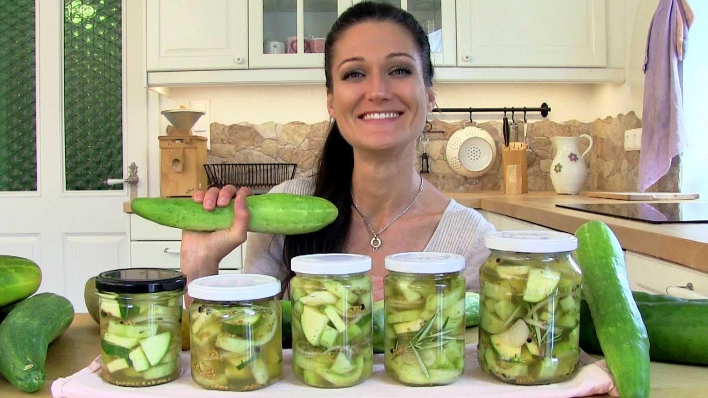 Am Bild befinden sich 5 Gläser mit eingelegten sauren Gurken und im Hintergrung ist Lana zu sehen, die eine frische Gurke in der Hand hält.