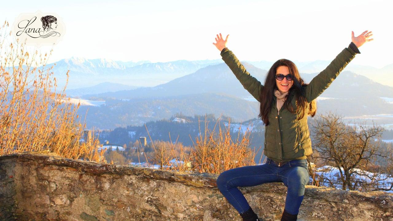 Lana sitzt auf einer Mauer und freut sich