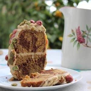 Auf einem österlich gedeckten Tisch ist ein Marmorkuchen-Osterei mit weißer Ganache überzogen und bunten Marzipanblumen darauf angeschnitten serviert. Man sieht so, dass es aus Marmorkuchen besteht.