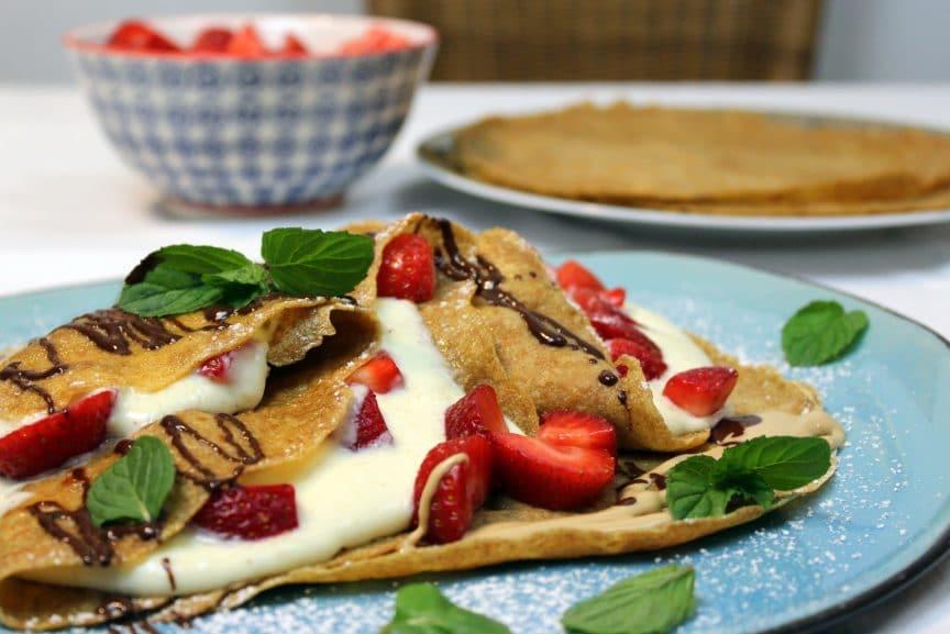 Palatschinken mit Vanillecreme und Erdbeeren auf einem Teller mit Schokosauce und Minzblätter angerichtet.