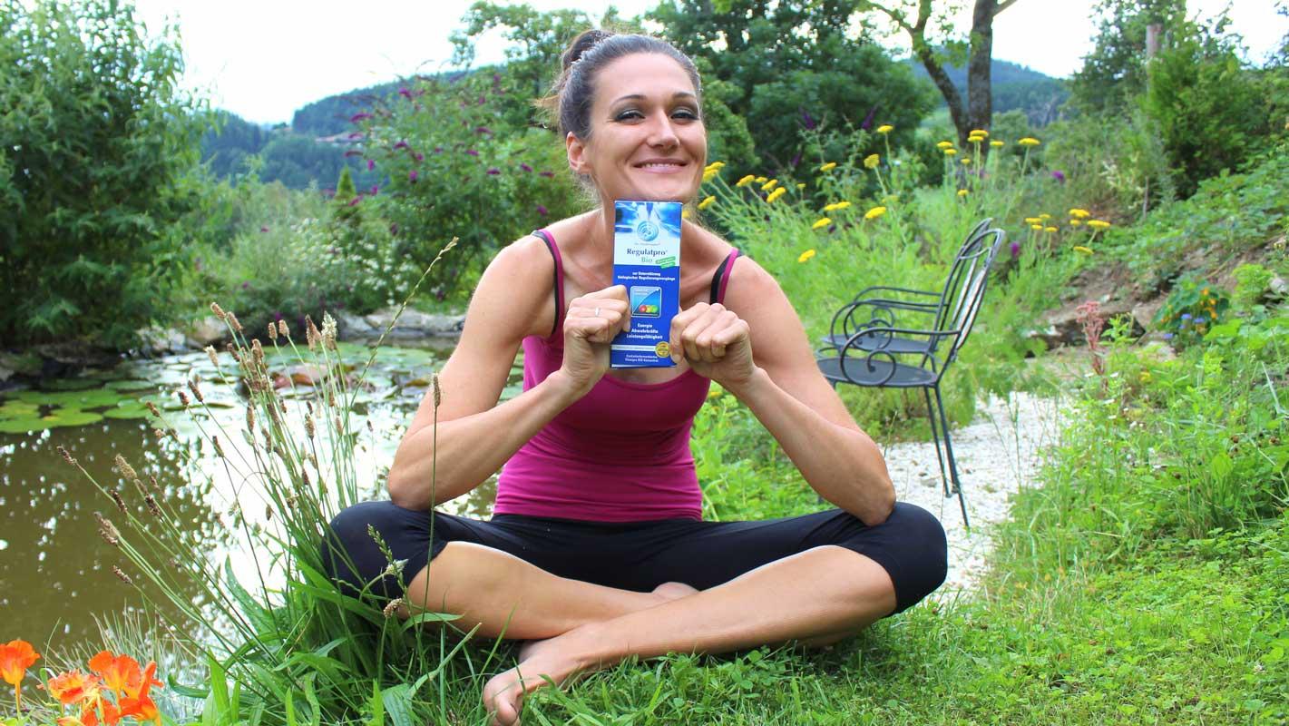 Lana sitzt im Garten und hält eine Flasche Regulatpro Bio in ihren Händen.