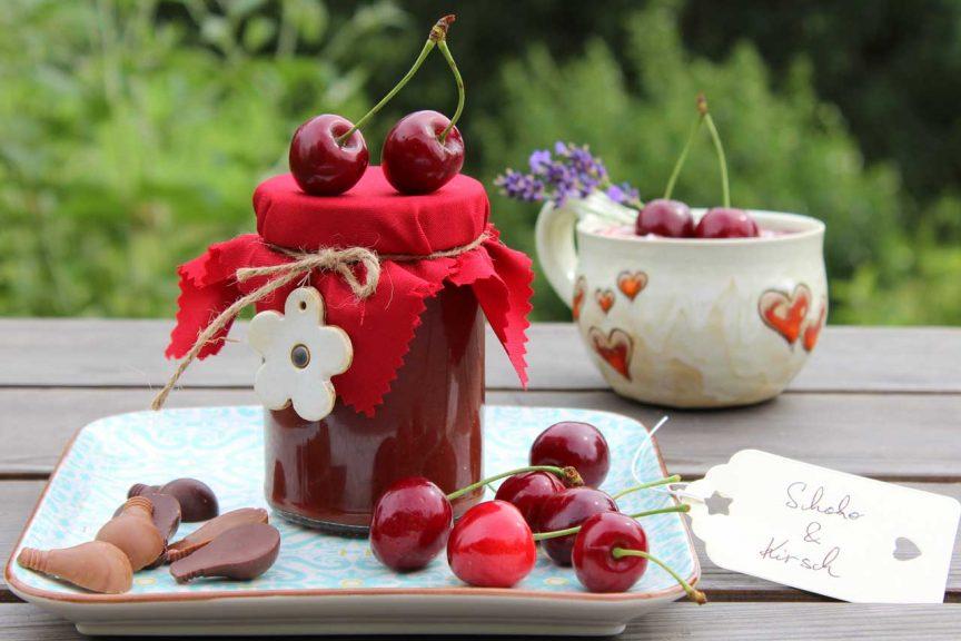 Auf dem Bild ist ein Glas Schoko-Kirsch-Marmelade, daneben liegen frische Kirschen und Schoko-Stücke. Dahinter ist eine Tasse mit Joghurt, in welches die Schoko-Kirsch-Marmelade eingerührt ist.