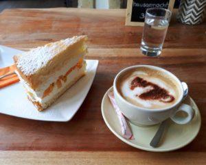 Topfentorte und Cappuccino stehen am Tisch im Katzencafé.