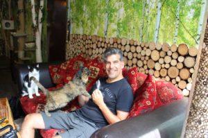 Matthias füttert eine Katze im Katzencafé.