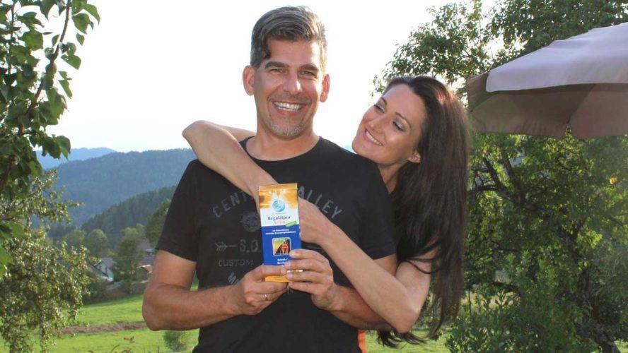 Lana steht mit ihrem Mann im Garten und er hält eine Flasche Regulatpro Arthro in der Hand.