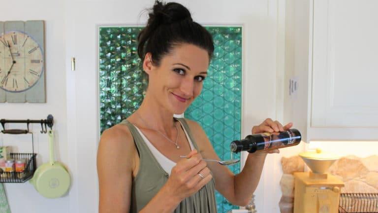 Lana schüttet hochwertiges Öl aus einer Flasche in einen Esslöffel zum Ölziehen.