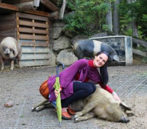 Lana streichelt ein Schwein im essbaren Tiergarten.