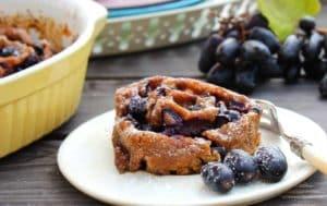 Auf dem Bild ist eine Trauben-Schnecke mit drei blauen Trauben auf einem Dessertteller zu sehen.