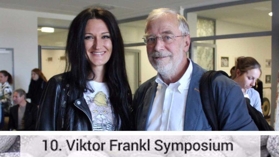 Lana steht neben Gerald Hüther am Viktor Frankl Symposium und beide sehen in die Kamera.