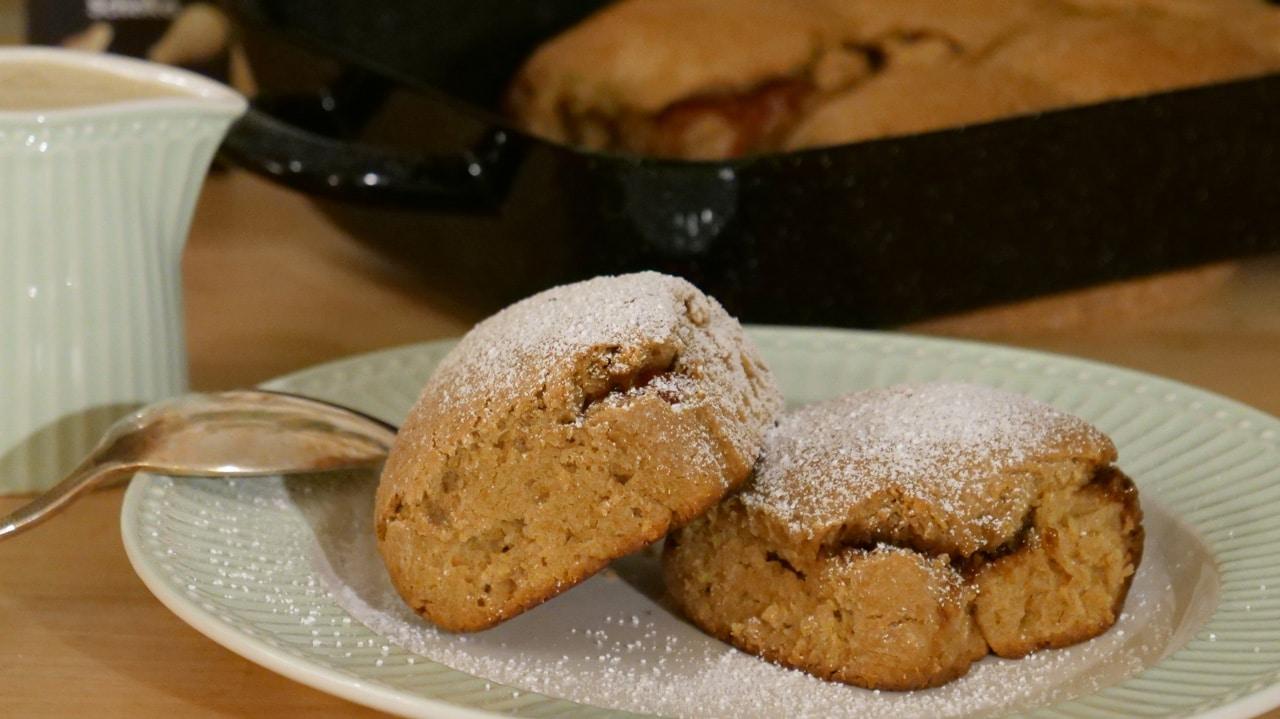 Zwei Buchteln mit Staubzucker bestreut sind auf einem Teller angerichtet. Daneben steht eine kleine Kanne mit Vanillesauce.