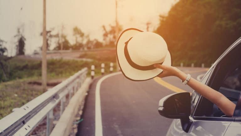 Eine Frau hält zum Zeichen ihrer Freiheit ihren Hut aus dem fahrenden Auto.