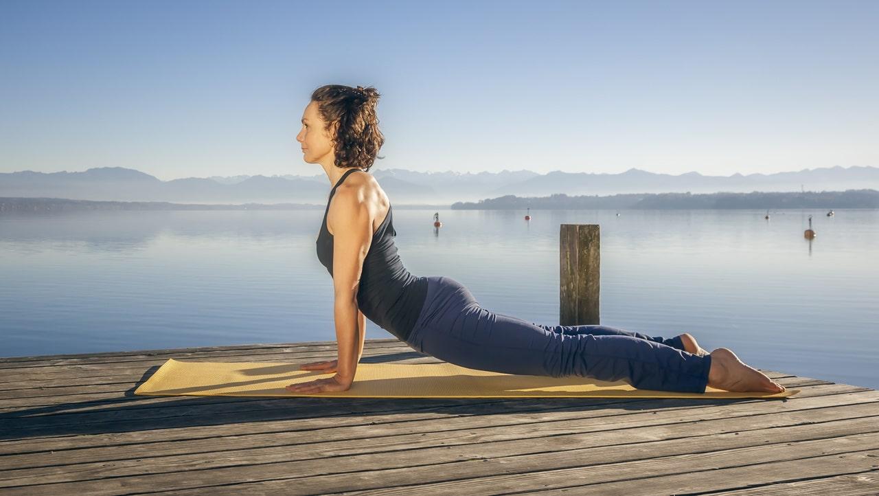 Eine Frau macht auf einer Yoga-Matte Übungen für den Rücken.