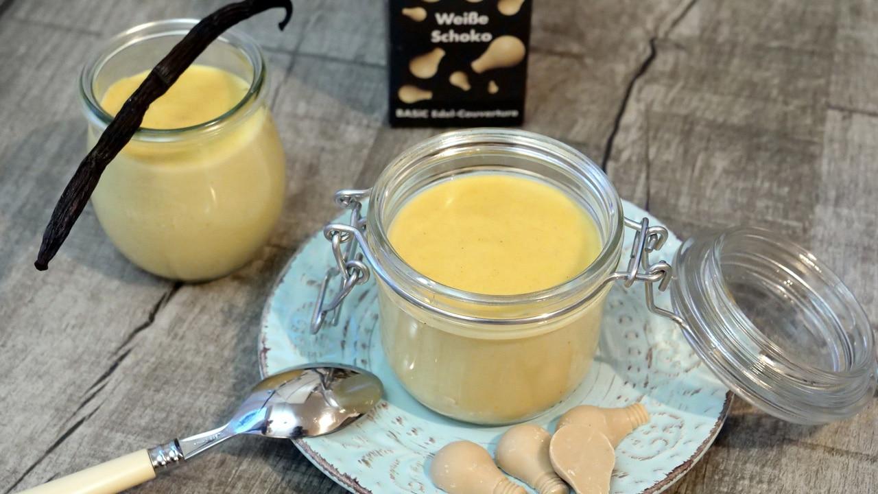 Auf dem Tisch stehen zwei schöne Gläser mit Vanillepudding. Als Deko ist weiße Schokolade und eine Vanilleschote zu sehen.