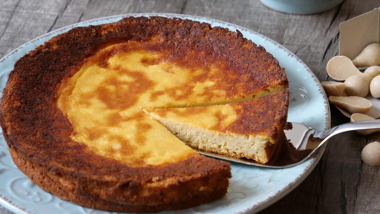 Ein runder Topfenkuchen ist angeschnitten auf einem Teller angerichtet.