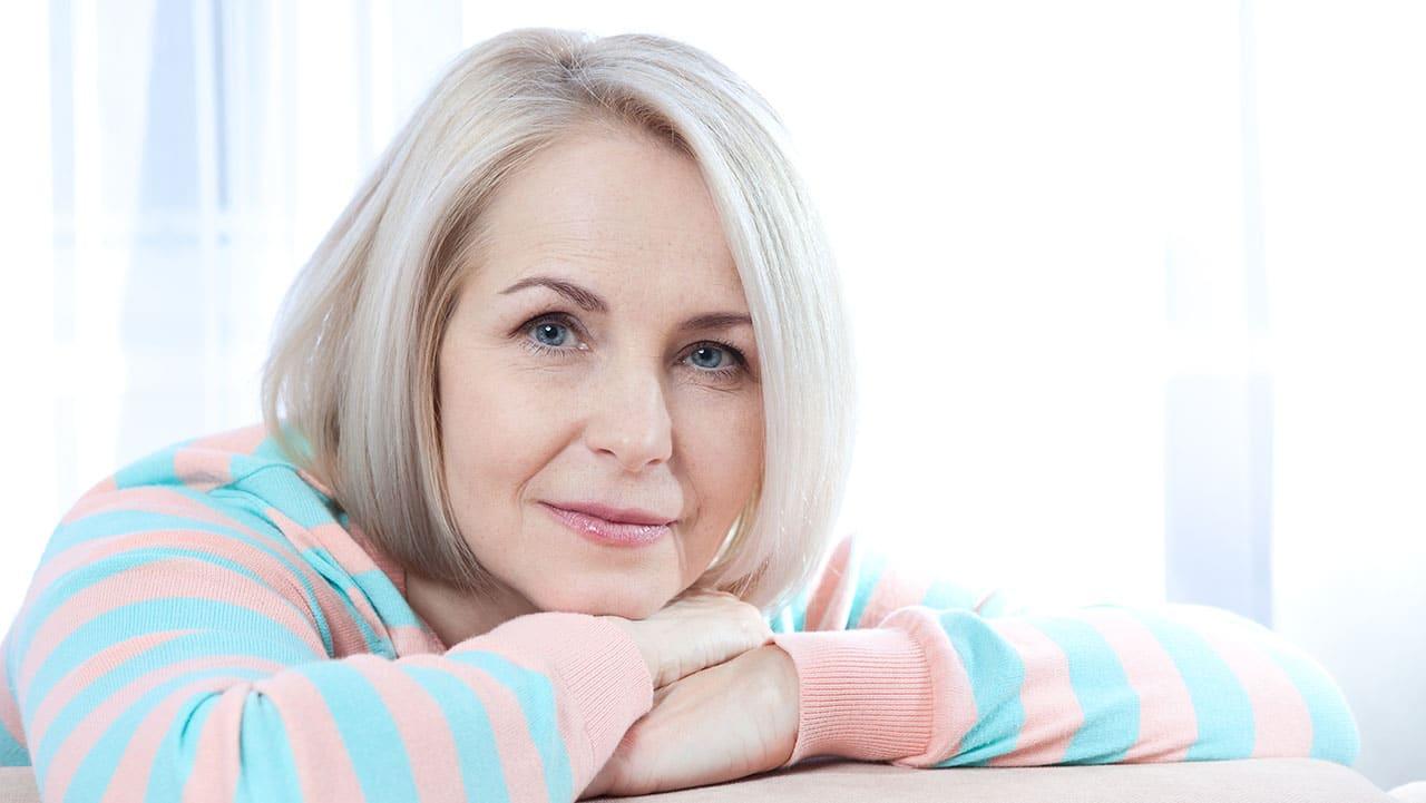 Eine etwa 50-jährige Frau sieht entspannt lächelnd in die Kamera. Sie hat offensichtlich einen guten Umgang mit ihrem Alter und den Wechseljahren.