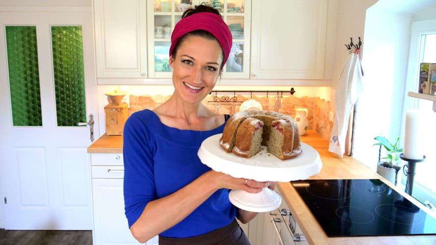 Auf dem Bild hält Sandra einen weißen Tortenteller, auf dem ein angeschnittener Kirsch-Gugelhupf mit Mohn und weißer Schokolade steht.