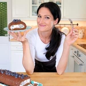 Sandra hält ein Teller hoch, auf dem ein Stück ihrer selbstgemachten Schoko-Heidelbeer-Roulade ist.