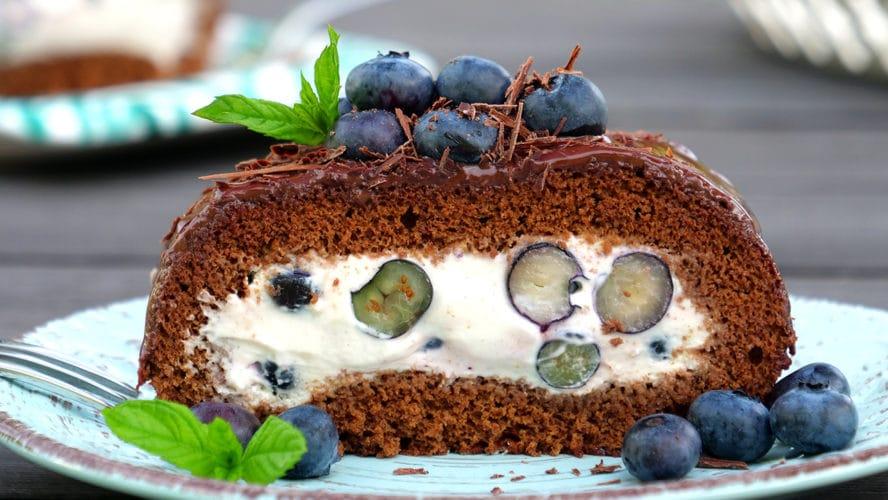 Ein Stück von der Schoko-Heidelbeer-Roulade ist auf einem Teller angerichtet. Sie ist mit Schokospäne und Heidelbeeren garniert.