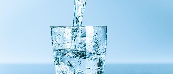 Leitfaden zur Detoxkur - Jemand gießt Wasser in ein Glas