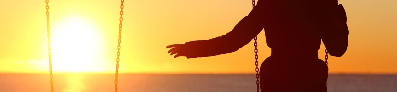 Eine Frau auf einer Schaukel und der Sonnenuntergang