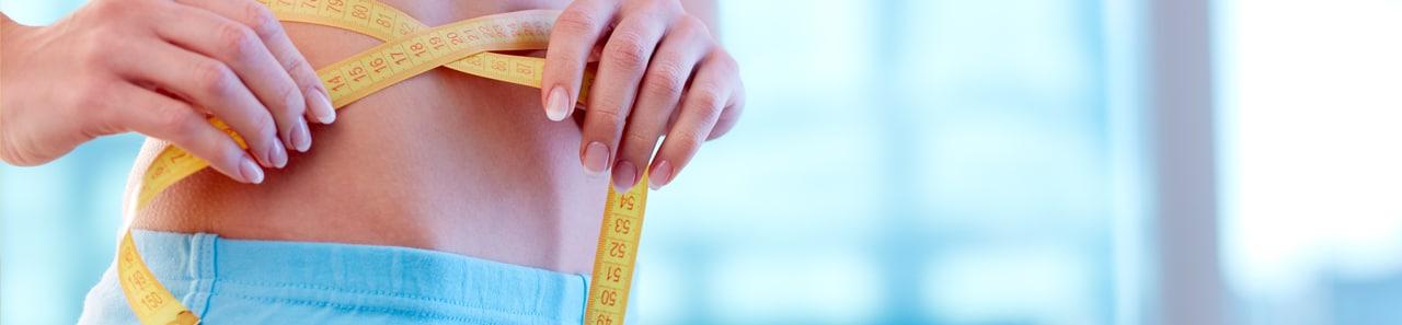 Eine Frau mit einem Maßband am Bauch