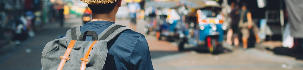 Ein Mann auf internationaler Reise von hinten mit Rucksack