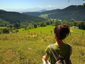 Sandra Exl blickt in das Tal vom Urlaub am Bauernhof Schlinthof in Liebenfels, Österreich
